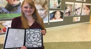 Cardinal Stritch Art teacher Lauren Hurd shows the Cardinal Coloring Book created by students in her Art 1 class.