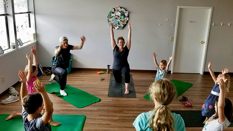 Good Grief Summer Camp students practice yoga with instructor Erin Marsh.