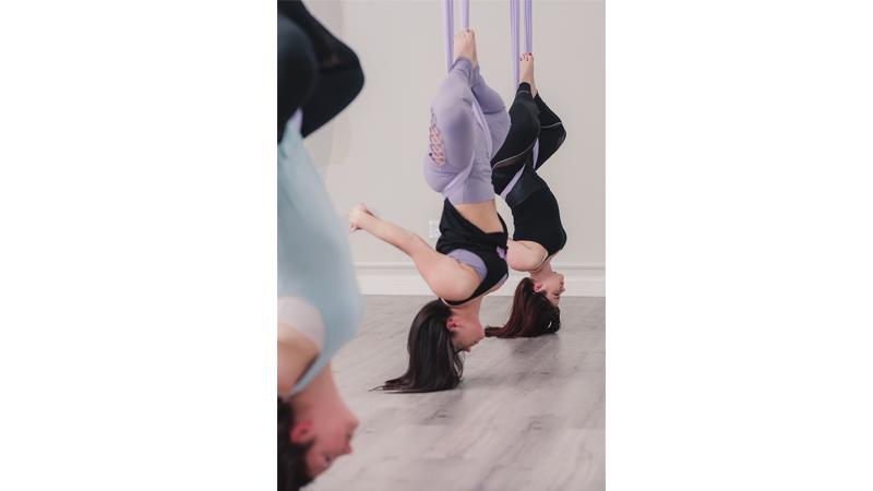 Aerial students looking at life upside down at Yogaja Yoga