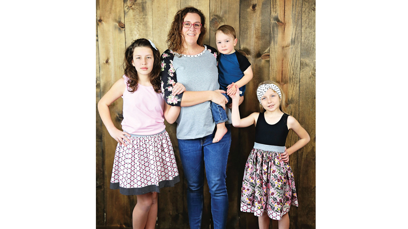 Kathy McKnight Pietrowski is pictured with her three stylish children sporting her very own designs.