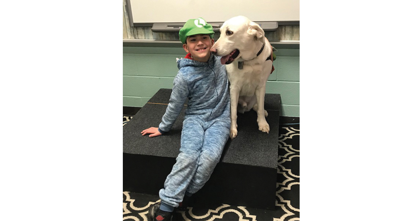 "In March, a ""hat day"" fundraiser at Devin's school (above) raised additional funds for the therapy dog."