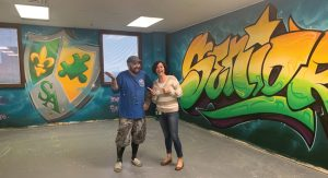 Graffiti artist Tony Touch joins Summit Academy Toledo principal Dawn Heck in front of wall art.