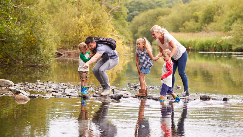 family-crossing-river-whilst-hiking