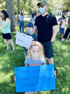 Erin's daughter, Camille, holding a sign at a recent protest (husband Alex and son Dexter behind her).