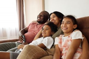 happy-family-sitting-on-a-couch-and-watching-tv-4260639-min